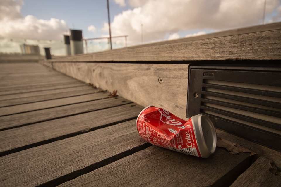 A Coke can lying on the street instead of being recycled.
