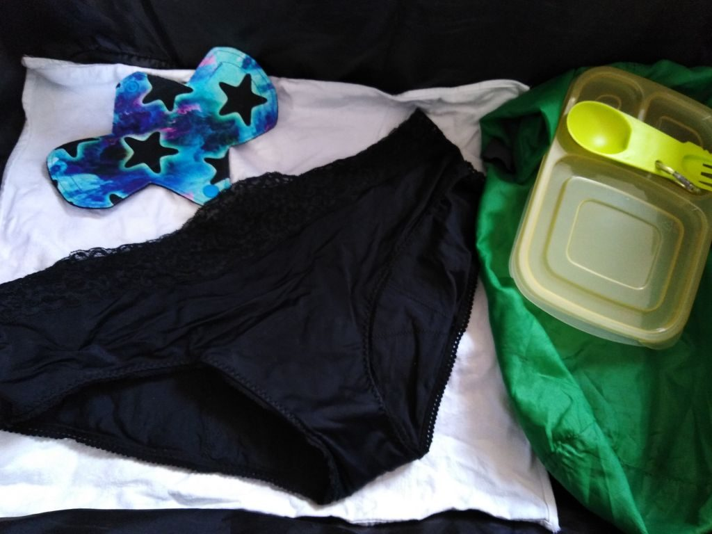 Suitcase with period pants, reusable pads, cloth napkin, lunchbox, spork, and kayak bag