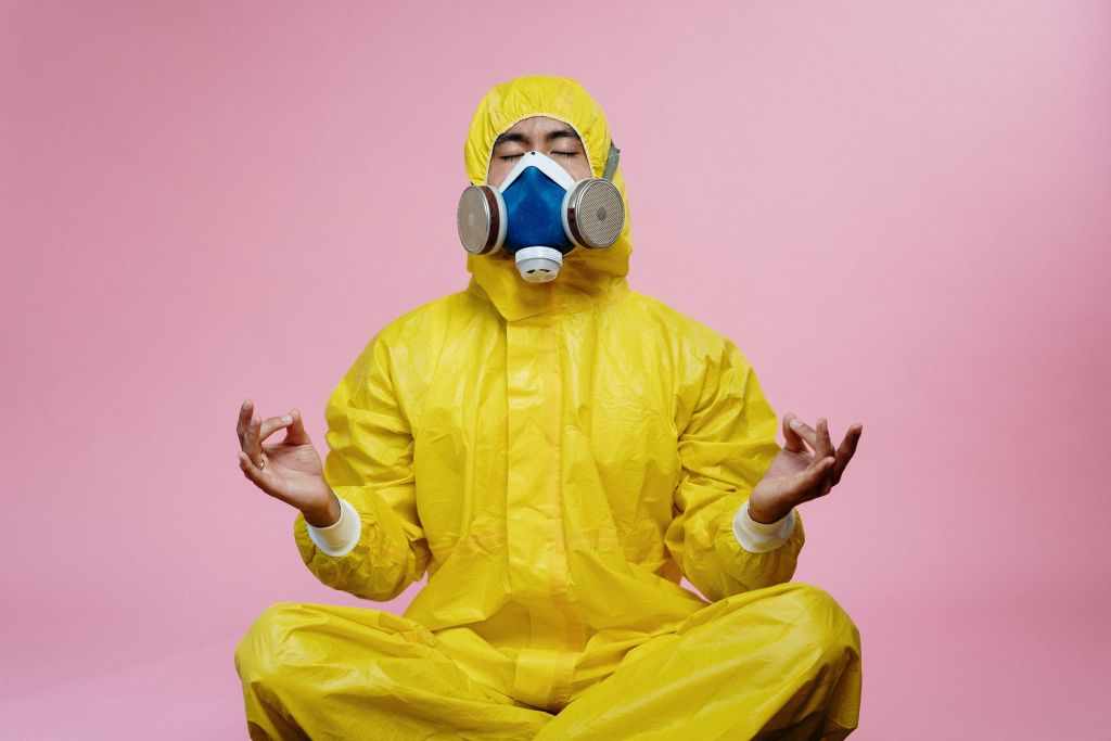 Image of person in a yellow protective suit and gas-style mask in a seated meditative yoga pose